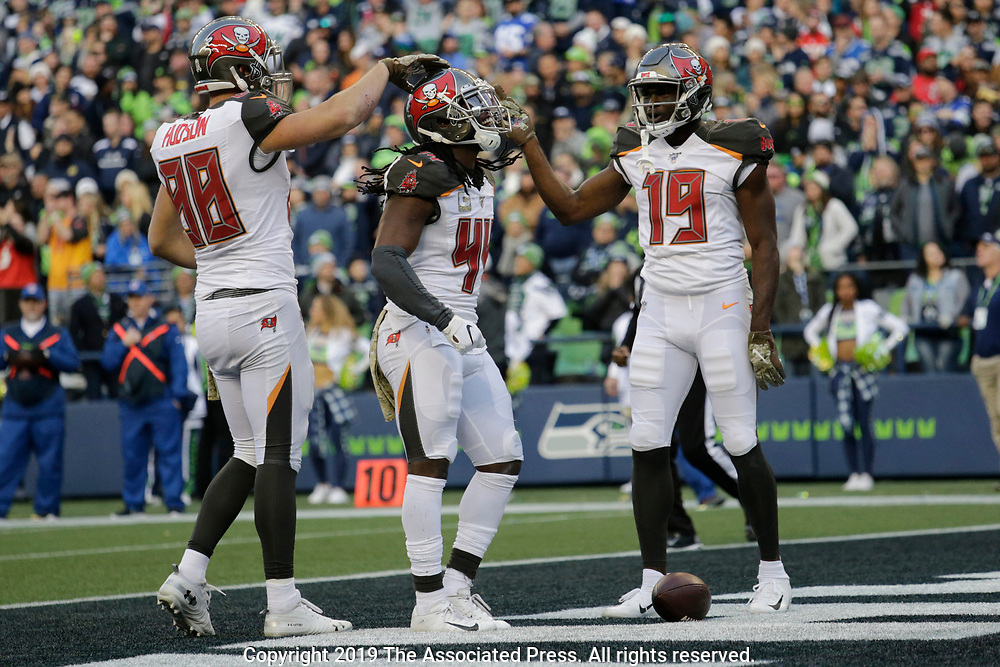 Tampa Bay Buccaneers running back Dare Ogunbowale, center, celebrates with wide receiver Breshad Perriman (19) and tight end Tanner Hudson (88) after Ogunbowale rushed for a touchdown against the Seattle Seahawks during the second half of an NFL football game, Sunday, Nov. 3, 2019, in Seattle. (AP Photo/John Froschauer)