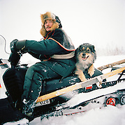 A Sami man with his dog on a snowmobile in Lapland, Sweden