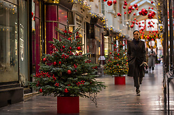 © Licensed to London News Pictures. 24/11/2020. LONDON, UK.  A woman out and about takes in the Christmas decorations that are on display in Burlington Arcade in Mayfair.  The shops are currently closed and will reopen once England's lockdown restrictions are eased by the UK government after 2 December.  Photo credit: Stephen Chung/LNP