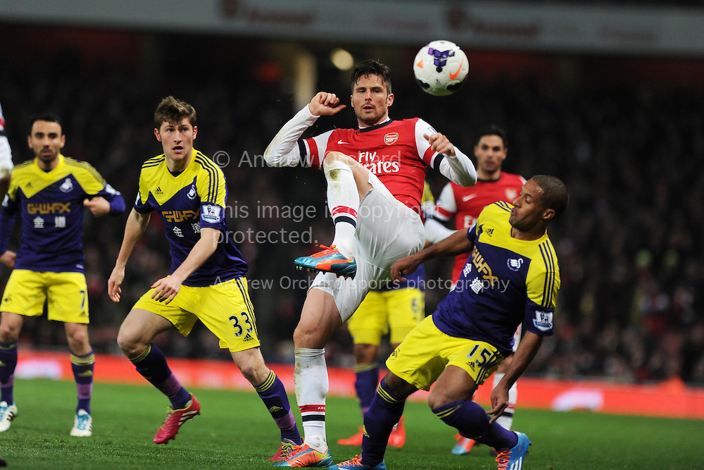 Arsenal's Olivier Giroud is challenged by Swansea's Wayne Routledge ®. Barclays Premier League, Arsenal v Swansea city at the Emirates Stadium in London, England on Tuesday 25th March 2014.<br /> pic by Andrew Orchard, Andrew Orchard sports photography.