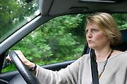 Fenella Hodson driving near her home, Godalming, UK. (Material World Family from Great Britain UK) MODEL RELEASED.