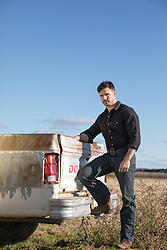 hot man by an old pick up truck out in a field