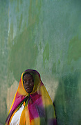 Girl from Makua tribe poses by Ilha de Mozambique Great Mosque wall