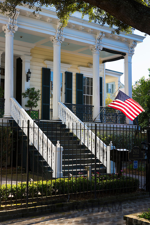 Traditional neo-classical clapboard grand house with columns, stars and stripes flag in the Garden District, New Orleans, USA