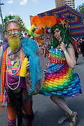 A man in a multicolored Neptune costume and a women in a dress made of balloons.