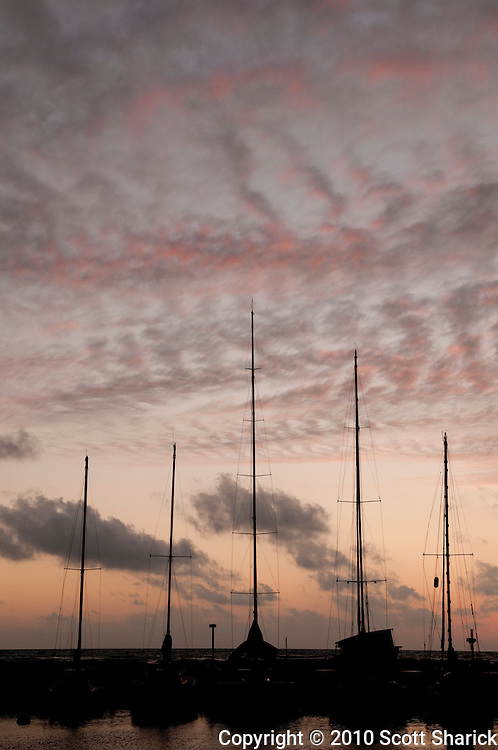 The sunset sky silhouettes boat masts at the Ala Wai Boat Harbor in Waikiki.