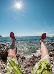 THEMENBILD - URLAUB IN KROATIEN, männliche Füsse in Richtung Meer gestreckt, aufgenommen am 03.07.2014 in Vrsar, Kroatien // male feet stretched towards the sea near Vrsar, Croatia on 2014/07/03. EXPA Pictures © 2014, PhotoCredit: EXPA/ JFK