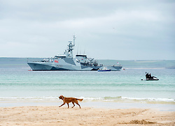 © Licensed to London News Pictures; 11/06/2021; St Ives, Cornwall UK. G7 summit in Cornwall. A dog passes along Porthminster Beach with HMS Tamar in the background at a protest by Extinction Rebellion in St Ives on the first day of the G7 summit. Photo credit: Simon Chapman/LNP.