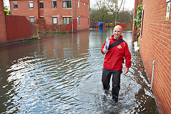 © Licensed to London News Pictures.  09/01/2014. OXFORD, UK. Postman Mike Nottage, who has being delivering letters for 25 years, wades through flood water in South Oxford.  Photo credit: Cliff Hide/LNP