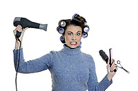 studio shot portraits of a young anguish funny and cute woman on a white background being a hair-curlers victim