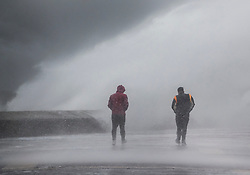 © Licensed to London News Pictures. 09/02/2020. Portsmouth, UK. Two men get a soaking from the waves during high tide at Southsea, Portsmouth as Storm Ciara batters the UK. Airlines have cancelled dozens of domestic and international flights as the storm brings strong winds and rain. Photo credit: Peter Macdiarmid/LNP
