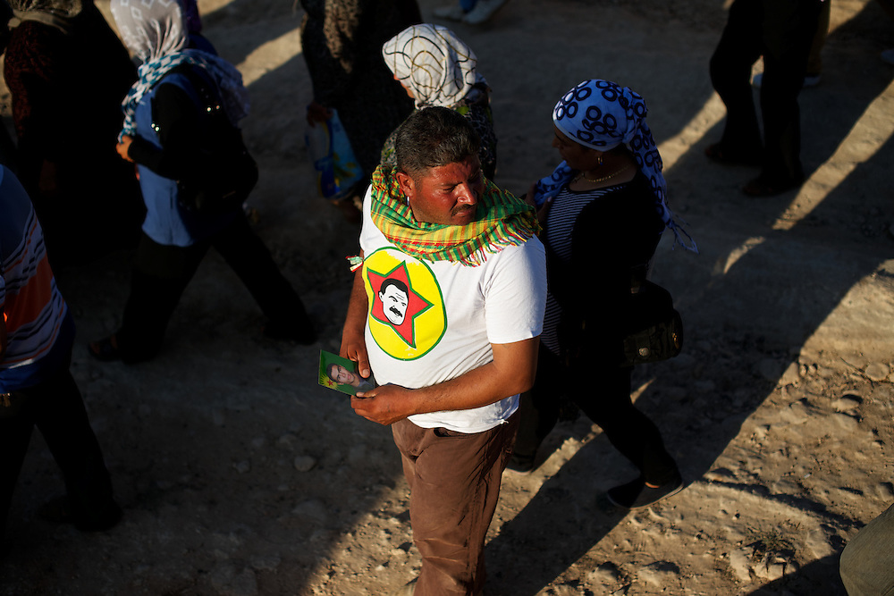 August 12, 2012 - Kafa Safra, Efrin, Syria: A Syrian Kurdish man passes by wearing a t-shirt with the face of the Kurdistan Workers' Party (PKK) leader, Abdullah Öcalan...PKK has been fighting an armed struggle against the Turkish state for an autonomous Kurdistan and greater cultural and political rights for the Kurds in Turkey, Iraq, Syria and Iran. Founded on 27 November 1978 in the village of Fis, was led by Abdullah Öcalan. The PKK's ideology was originally a fusion of revolutionary socialism and Kurdish nationalism - although since his imprisonment, Öcalan has abandoned orthodox Marxism. The PKK is listed as a terrorist organization by Turkey, the United States, the European Union and NATO. (Paulo Nunes dos Santos)