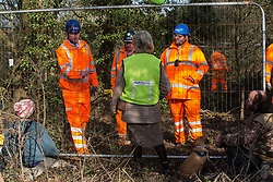 Harefield, UK. 7 February, 2020. Activists monitor HS2 engineers erecting Heras fencing to surround three environmental activists from Extinction Rebellion who have climbed a veteran oak tree close to the Harvil Road wildlife protection camp in order to try to protect it from felling. HS2 are expected to try to fell large numbers of mature trees in the immediate vicinity over the weekend even though the high-speed rail link is still awaiting Boris Johnson's approval.