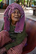 An old woman sits at a table. Angkor Wat, Siem Reap, Cambodia.