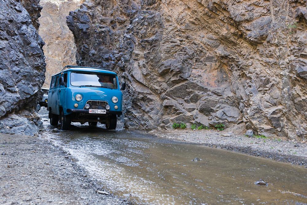A Russian van drives through a narrow passage near the Yolyn Am Valley, Mongolia. Photo © Robert van Sluis - www.robertvansluis.com