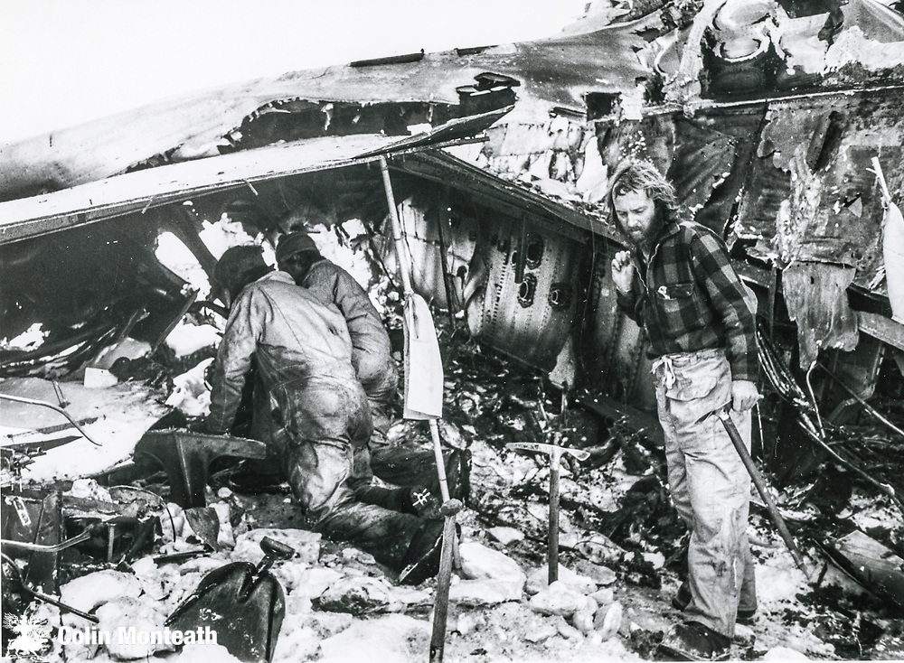 Mountaineer Harry Keys beside main fuselage, two policemen digging under wing Final day recovery operation, Air New Zealand crash December 1979.