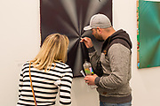 New York, NY - May 3, 2019. A man examines works by Anoka Faruqee and David Driscoll in the Koening + Clinton Gallery at the Frieze Art Fair on New York City's Randalls Island.