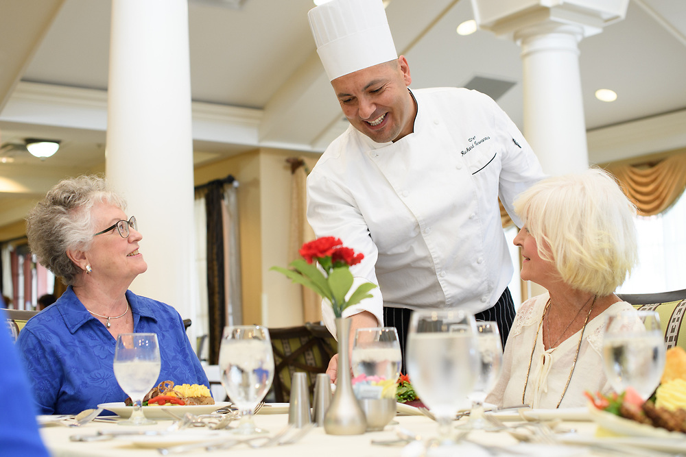 This is a lifestyle image of a chef delivering lunch to a group at a retirement community in Florida.