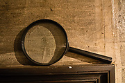 Magnifying glass on newsprint at Dove Cottage, Wordsworth's home. In Dove Cottage in the heart of the remote Lake District, William Wordsworth (1770–1850) wrote some of the greatest poetry in the English language and his sister Dorothy kept her 'Grasmere Journal', displayed in the Museum. Visit Dove cottage in Grasmere, Cumbria county, England, United Kingdom, Europe. England Coast to Coast hike day 5 of 14: Grasmere to Ullswater. [This image, commissioned by Wilderness Travel, is not available to any other agency providing group travel in the UK, but may otherwise be licensable from Tom Dempsey – please inquire at PhotoSeek.com.]