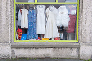 The window of a charity shop that sells bric a brac items and second-hand vintage dresses, on 3rd October 2021, in Beaumaris, Anglesey, Wales.