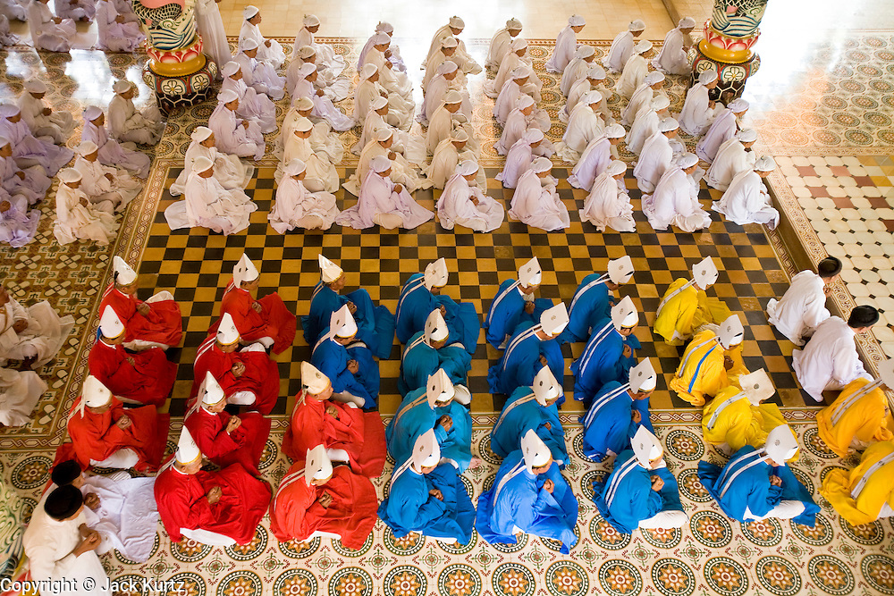 """10 MARCH 2006 - TAY NINH, VIETNAM: Noon Services at the main Cao Dai temple in Tay Ninh, Vietnam. The Cao Dai complex in Tay Ninh is the sect's headquarters. The Cao Dai religion is a blending of Buddhism, Confucianism, Taoism, Christianity and Islam. There """"saints""""  include Chinese leader Sun Yat Sen and French author Victor Hugo. There are about two million members of the Cao Dai religion in Vietnam. British author Graham Greene, who wrote about the Cao Dai in the """"The Quiet American"""" said the relegion was """"a Walt Disney fantasia of the East."""" The Cao Dai pray four times a day - midnight, 6AM, noon, 6PM.  Photo by Jack Kurtz / ZUMA Press"""