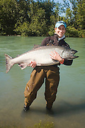 USA. Alaska. Kenai Peninsula. Kenai Alaska, Kenai River.  King Salmon fisher holding a fresh caught large King.  Colorful cloths, beautiful sunshine on the Kenai River. Pretty woman. MR