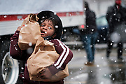 23 NOVEMBER 2020 - DES MOINES, IOWA: A child volunteering at a food distribution carries bags of food to people in line during a Thanksgiving food distribution at a park in Des Moines during a snowstorm. The food distribution was organized by Urban Dreams, a community empowerment NGO in central Des Moines, and the NAACP. The food was provided by Hy-Vee, a regional grocery store chain based in Des Moines. They had about 450 meals available. A spokesperson for Hy-Vee said the company was giving away more than 20,000 Thanksgiving meals this year. The Food Bank of Iowa said food insecurity in Des Moines has doubled since the start of the Coronavirus pandemic.   PHOTO BY JACK KURTZ
