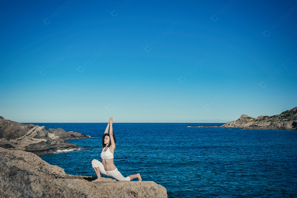 Low lunge yoga pose at the sea
