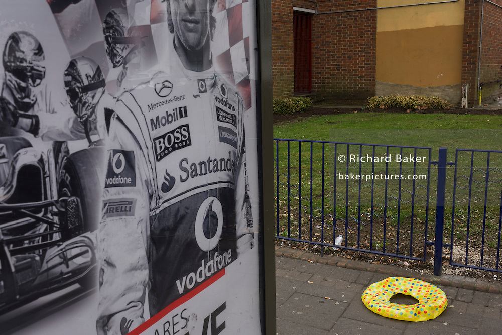 Racing driver Jenson Button wears suit adorned with sponsoship logos alongside abandoned beach ring in street.