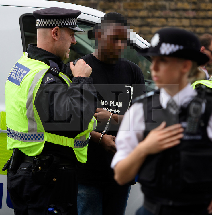 © Licensed to London News Pictures. 29/08/2016. London, UK. A young man being detailed by police as carnival goers enjoy day two of the Notting Hill carnival, the second largest street festival in the world after the Rio Carnival in Brazil, attracting over 1 million people to the streets of West London.  Photo credit: Ben Cawthra/LNP