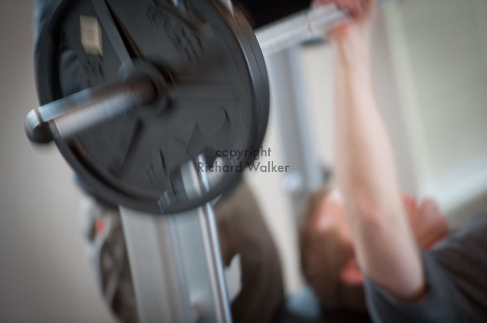 2012 March 30 - Man in exercise room lifting weights, Seattle, WA USA. By Richard Walker