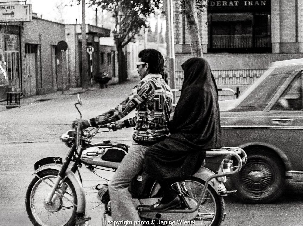 Woman in chador ( hijab ) riding on motorbike, Tehran Iran 1970s