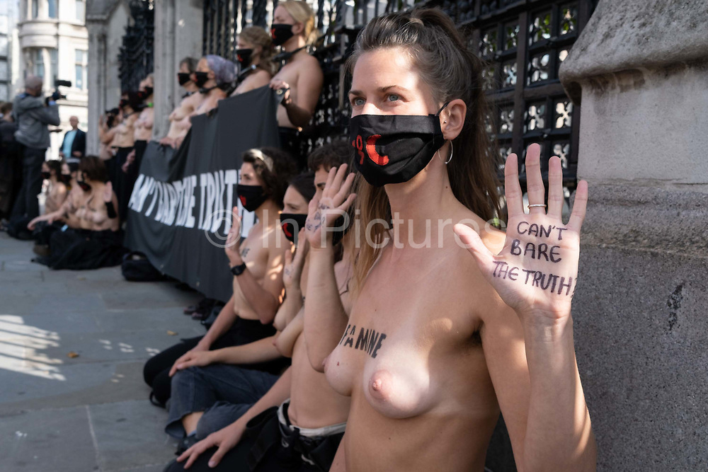 Thirty topless women supporters of Climate Change activists, Extinction Rebellion protest outside the UK parliament railings, on 10th September 2020, in London, England. Locked with D-locks around their necks, their banner reads 'Can't Bare the Truth?' and wearing face masks branded with '4°C', the women were removed and arrested then loaded into police vans where they placed their hands on the windows with the same slogan.