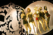 An adult business window displays the naughty underwear worn by five mannequin models of a Soho sex shop on Old Compton Street in London's West End. Tilted slightly to the left, we see the 5 models posing in various positions of suggestive stances, all demonstrating the shop's array of erotic clothing for the Good Time Girl! On the far right is the artwork of a topless woman, wearing only knee-length stockings. See from behind, the line-drawing of the female suggests a dancer on a Parisian stage act such as the Folies Bergere or Paradis Latin - variety performances for the male admirer. She looks over her left shoulder as if to wink in our direction, all part of the illusion of coquettish desire and greedy eroticism. Old Compton Street is known for cafes, bars and especially the gay, trans-gender scene and for sellers of erotic toy 'accessories'!
