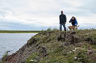 Syskonen Louie Green och Briday Green visar erodering vid floden som de anser ha blivit värre på senare tid. <br /> <br /> Nome, Alaska, USA<br /> <br /> Fotograf: Christina Sjögren<br /> <br /> Photographer: Christina Sjogren<br /> Copyright 2018, All Rights Reserved