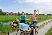 In de omgeving van Groenekan fietsen twee jongens met visspullen.<br />