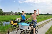 In de omgeving van Groenekan fietsen twee jongens met visspullen.<br /> <br /> Near Groenekan two boys are cycling with fishing gear.