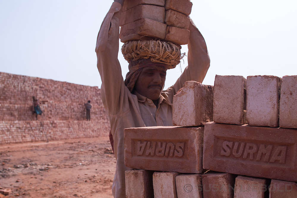 Man carries a stack of bricks on his head to transport to another location in the factory, Bangladesh.