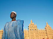 A man in traditional dress outside the Great Mosque of Djenné, the worlds largest mud built structure and UNESCO heritage site, at Djenné, Mali