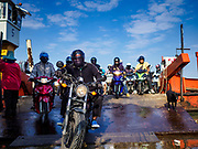 22 JANUARY 2019 - PHRA PRADAENG, SAMUT PRAKAN, THAILAND: Passengers disembark from a motorcycle and vehicle ferry that crosses the Chao Phraya River in Phra Pradaeng, in the suburbs south of Bangkok. The use of vehicle ferries across the river has gone down as the government has built bridges to connect communities on both sides of the river. The Phra Pradaeng ferries are the busiest vehicle ferries in the Bangkok metropolitan area. Since the BTS Skytrain now comes close to the ferry, the number of commuters going into Bangkok that use the ferry has increased.     PHOTO BY JACK KURTZ