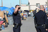 Under police guard on roped-off streets, contractors hired by the city of Salinas clean out homeless encampments on Thursday, March 24th in the Market Way area of Chinatown.