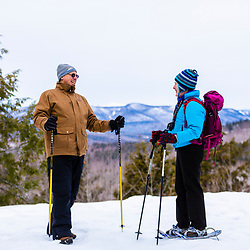 A man and woman take a break from snowshoeing at Loon Echo Land Trust's Bald Pate Mountain Preserve in South Bridgton, Maine.