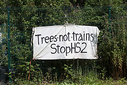 Harefield, UK. 22 July, 2020. A banner pinned to a site fence by environmental activists during tree felling for the HS2 high-speed rail link alongside Harvil Road. Environmental activists from Stop HS2 and HS2 Rebellion continue to protest against HS2, which is currently projected to cost £106bn and will remain a net contributor to CO2 emissions during its projected 120-year lifespan, from a series of wildlife protection camps along its route.