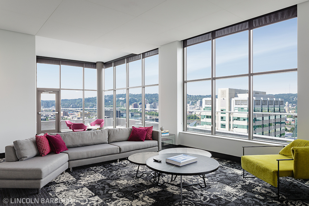 A living room with modern looking furniture in high rise building.  Lots of windows give a nice view of Portland, Oregon.