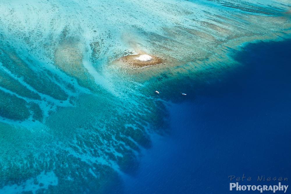Aerial view of large, colorful coral reef surrounding tiny white sandbar island with two boats nearby