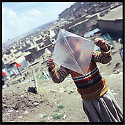 Saboor, 6, one of Noor Agha's sons, plays with his plastic kite next to his house inside the graveyard in Kabul, Afghanistan, Saturday, March, 10, 2007. Noor Agha is a renowned kite maker who made kites for the movie makers of the best-selling novel, The Kite Runner, which will be distributed by Dreamworks and Paramount Vantage in Nov. this year. Noor Agha's wives, using their special glue, help him produce enough kites to please the clients' needs. Some of his children can also make their own kites with plastic bags and bamboo sticks. As the Afghan New Year's Day (Nawruz) approaching on March 21, the finger tips of Noor Agha's family got busier for mass production.