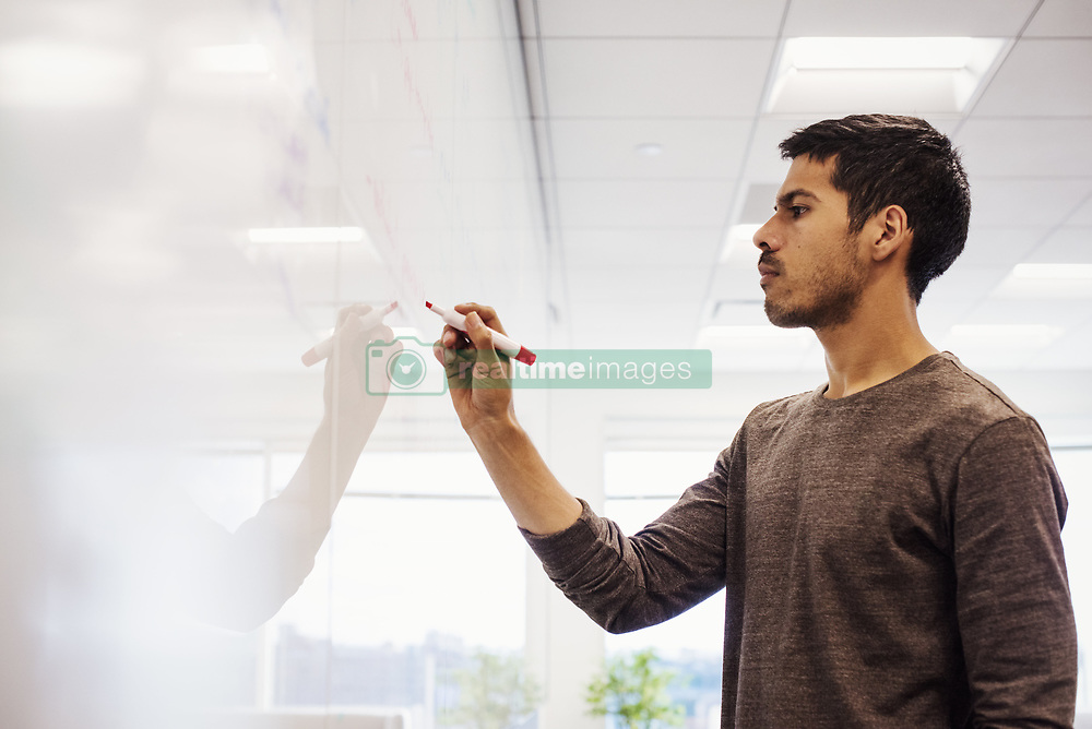 October 23, 2016 - A man standing in a classroom writing on a whiteboard. (Credit Image: © Mint Images via ZUMA Wire)