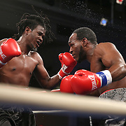 """Berthin Rousseau (dreadlocks) fights Howard Reece during the """"Boxeo Telemundo"""" boxing match at the Kissimmee Civic Center on Friday, March 14, 2014 in Kissimmme, Florida. (Photo/Alex Menendez)"""