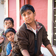 Portrait of three young Indian boys on a bike in old city of Jodhpur