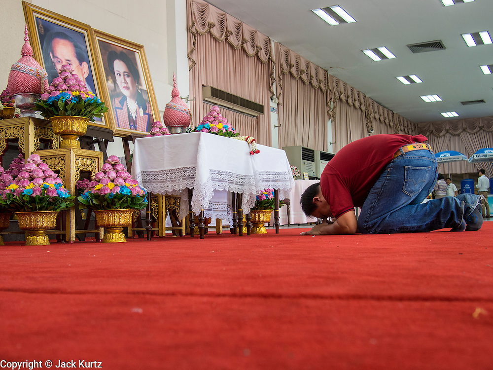 01 AUGUST 2013 - BANGKOK, THAILAND: A man prostrates himself in front of photos of Bhumibol Adulyadej, the King of Thailand, and his wife, Queen Sirikit, who have both been living in Siriraj Hospital. The King, 85, was discharged from the hospital, Thursday where he has lived since September 2009. He traveled to his residence in the seaside town of Hua Hin, about two hours drive south of Bangkok, with his wife, 80-year-old Queen Sirikit, who has also been treated in the hospital for a year.      PHOTO BY JACK KURTZ